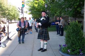 A bagpiper plays outside the doors of the church