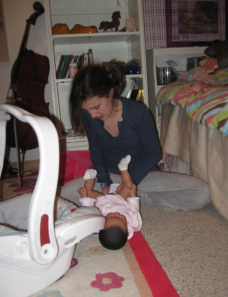 Hallie changing the RealCare® Baby's diaper