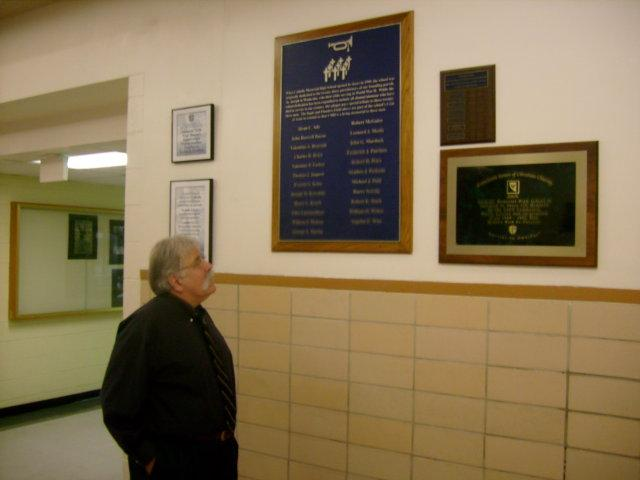 Pat Farrell studies the names of former Catholic Memorial students killed in action.