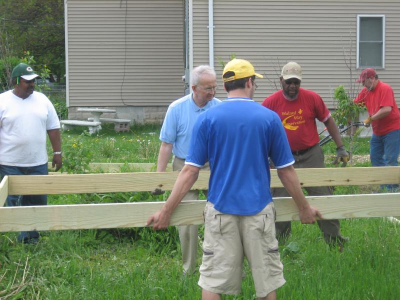 Rotaract volunteer and Carroll University senior Rafael Fernandes (front) helps Walnut Way Conservation Corp employees lay down a garden bed in their vegetable patch.