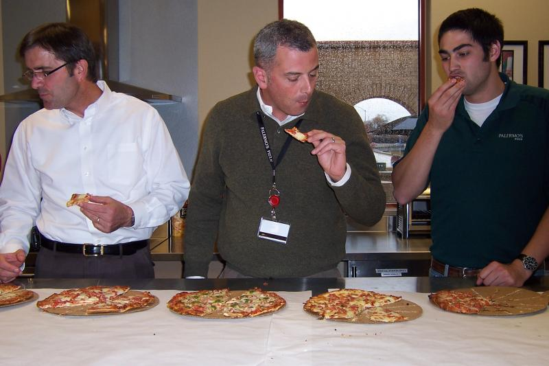 Chris Dresselhuys (center) and two other researchers taste pizzas at the Palermo's plant in Milwaukee, to ensure a quality product.