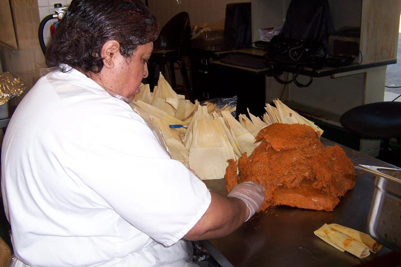 Martha Yepez stuffs pork into tamale husks at the El Rey plant in Milwaukee.