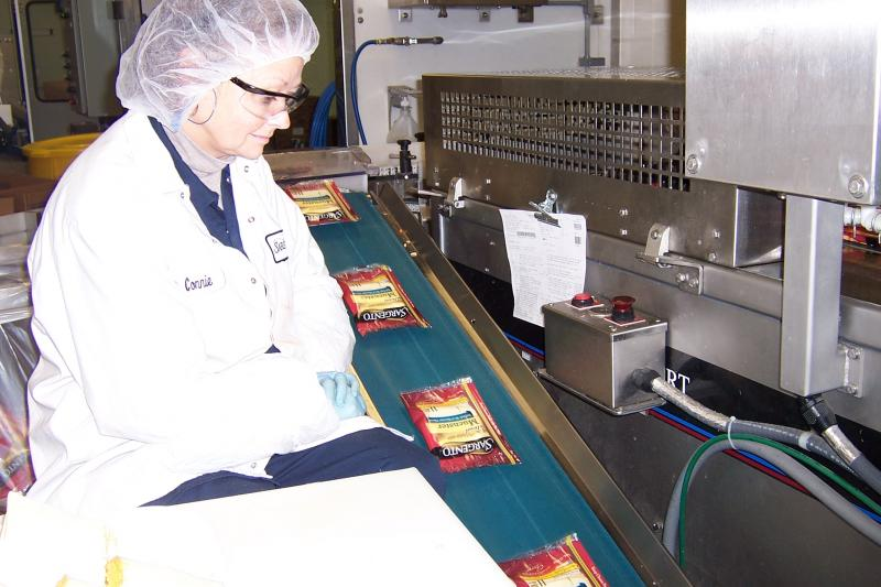 Employee Inspects Cheese at the Sargento Plant