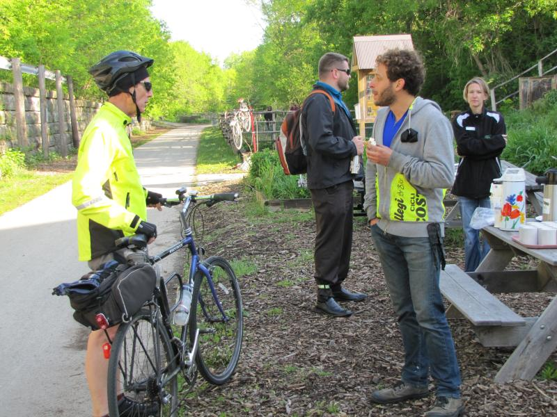 Evan Pack  (right) chats with commuters on Oak Leaf Trail. He's collecting and cleaning up donated bikes to encourage more people to cycle.