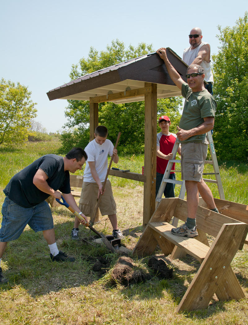 Mitchell Butschle (red shirt & cap)  works with fellow Eagle Scout and leaders to built a resting spot for hikers in Warnimont Park.