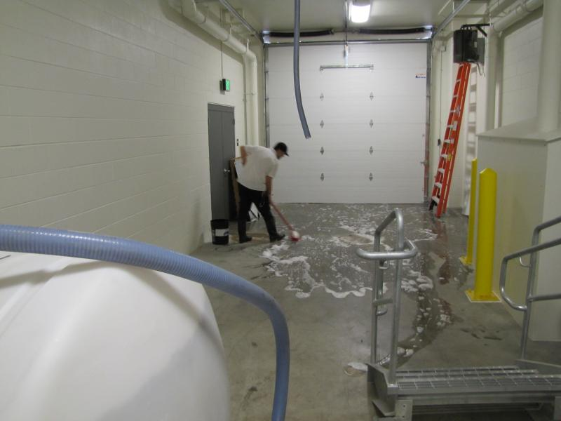 Clock Shadow Creamery cheesemaker cleans up after milk delivery.
