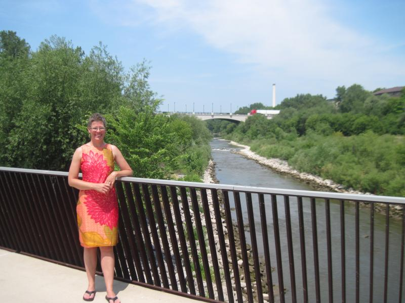 Kimberly Gleffe of the River Revitalization Foundation stands on a pedestrian bridge built on the old North Avenue Dam structure. The river upstream flows freely and is more narrow and shallow than the waterway to the south.