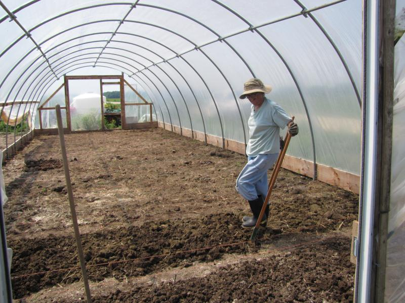 Farmer Brigid McGeehan prepares the shared hoop house for first planting