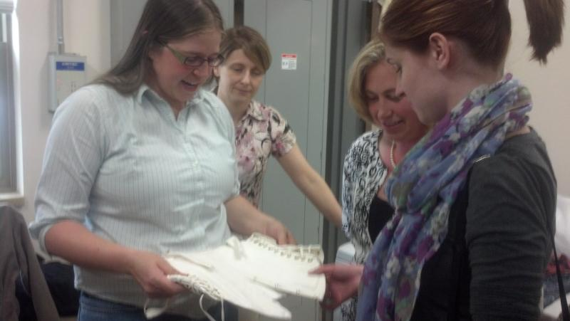 (l-r) Period Clothing Coordinator Rachel Neubauer and Curator of Interpretation Jennifer Van Haaften show Amy and Ashley Ziolkowski a corset style they can opt to wear.