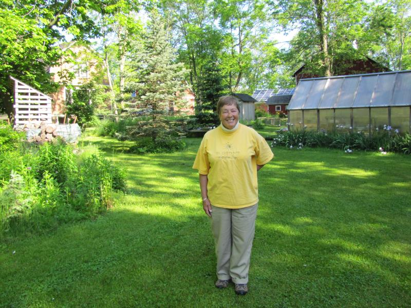 Sister Janet Weyker strolls the Eco-Justice Center grounds.  The greenhouse behind her was funded through a grant.  That's how much of the center's renewable and green projects have come to life.