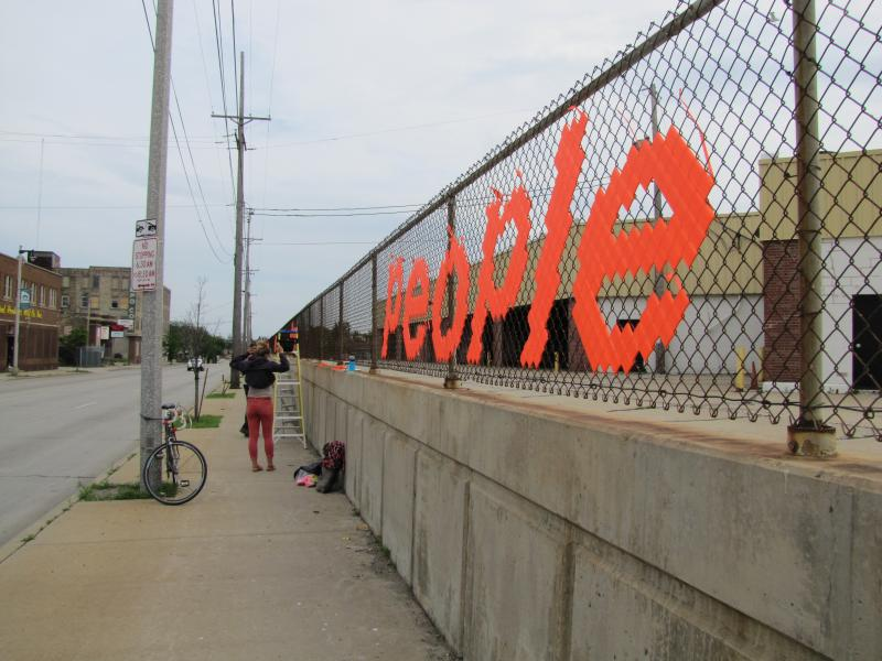 """Reeves stretches message """"Do Something Constructive - Help Other Perople"""" along county transit fence."""