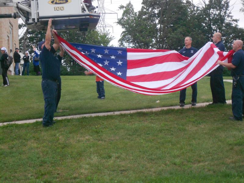 Oak Creek Police hanging the American flag.