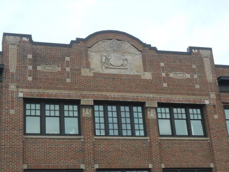 Above the bookstore is a relief of an old-fashioned car.