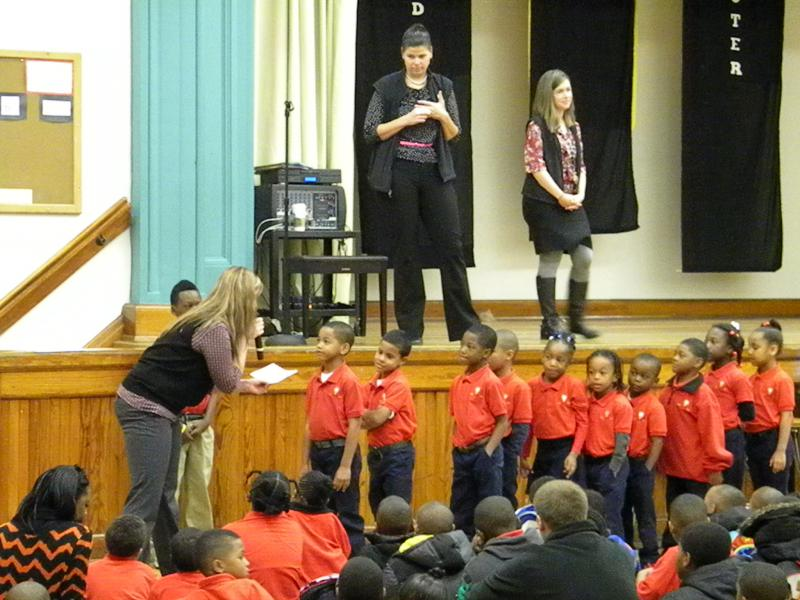 Principal Maggy Olson (center) speaking at a daily assembly with  Brittany Sanderson, dean of students on the stage and Allison Peterson, academic dean by the scholars.