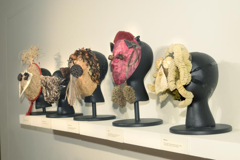 A row of masks made from found objects created by UW-Madison professor Beverly Gordon