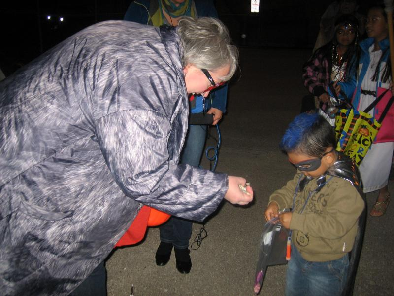Milwaukee mother Susan Wetrich hands out candy to 3-and-a-half year old Alaric Bucio at IDEAL School's trunk-or-treat on Friday, Oct. 25th.
