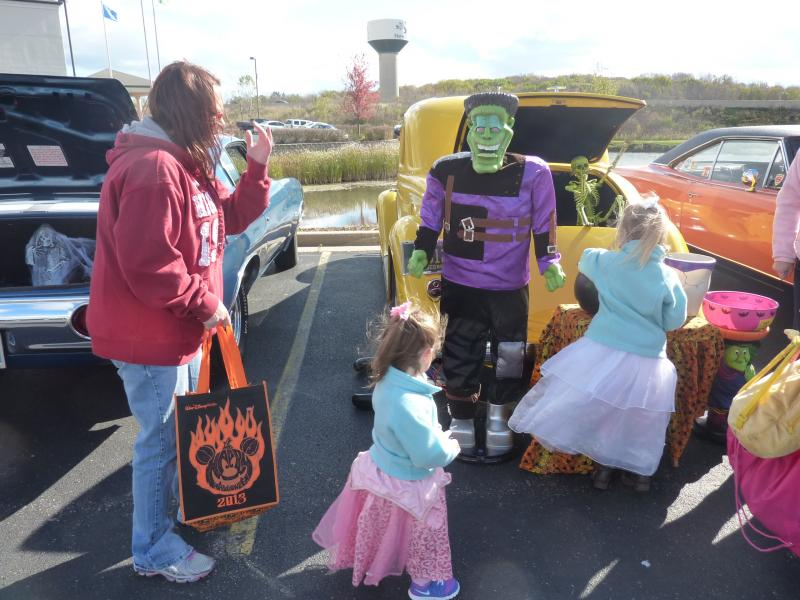 Princesses Isabella and Aubree get candy from a decorated trunk at the trunk-or-treat event at the car-themed restaurant Quaker Steak and Lube on Saturday, Oct. 26th in New Berlin.
