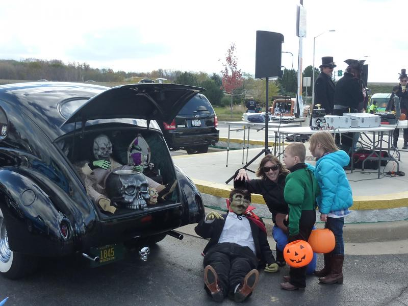 Peyton and Sienna Johnson with mom Jenelle of New Berlin check out a themed hot rod at the trunk-or-treat event at the car-themed restaurant Quaker Steak and Lube on Saturday, Oct. 26th.