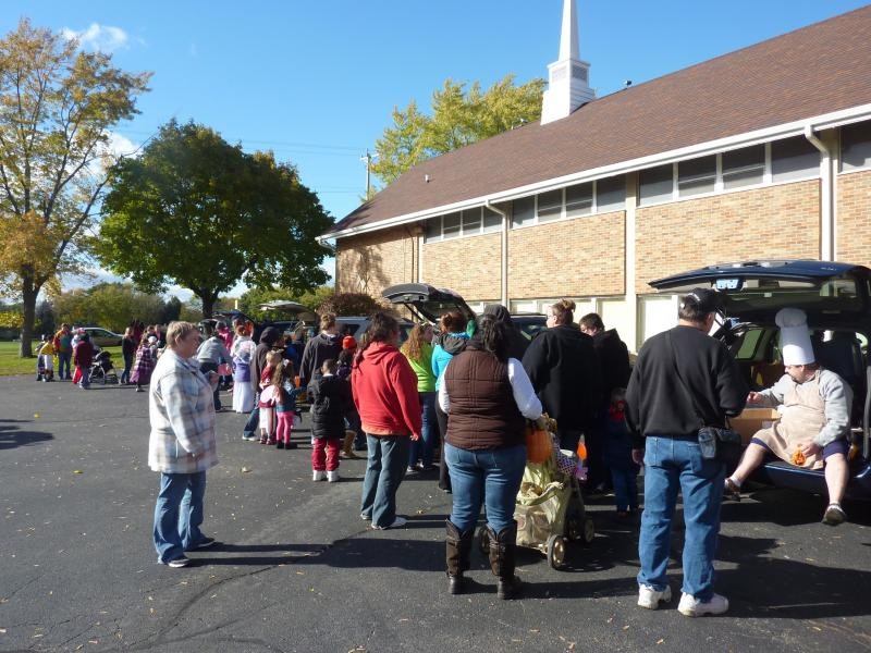 Trunk or treaters line up to get treats from the backs of cars in the parking lot of Messiah Evangelical Lutheran Church in Beloit, on Saturday, Oct. 26th. Pastor Jason Reed (far right) is dressed as a harried baker.