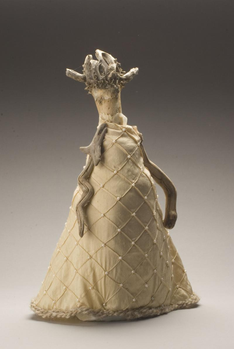 A stick is adorned with pearls and some fabric to create this doll-like sculpture.