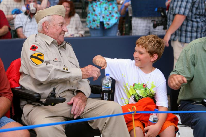 A veteran and a young man share a special moment at Miller Park as part of the Stars and Stripes Honor Flight program.