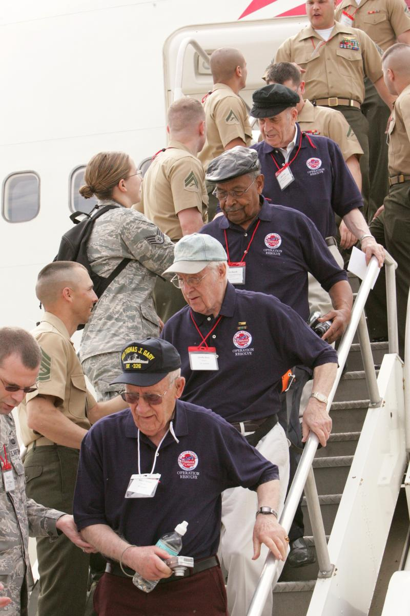 Service members welcome the WWII veterans, as they disembark the plane in Washington, D.C. on their way to the WWII memorial and Arlington National Cemetery.