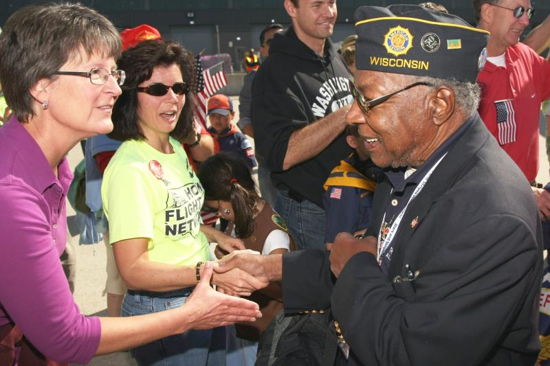 Volunteers and other greeters thank a Wisconsin veteran for his service during the Stars and Stripes Honor Flight program. The veterans went to the WWII memorial and Arlington National Cemetery in Washington, D.C.