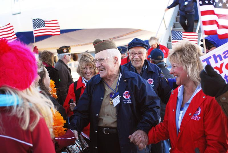 Volunteers and other greeters welcome veterans off the Stars and Stripes Honor Flight plane in Washington, D.C.