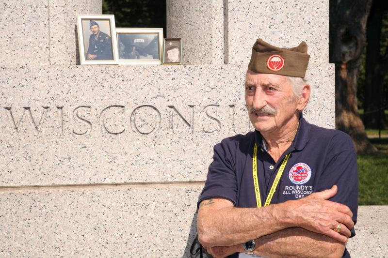 A Wisconsin veteran stands beside the WWII memorial in Washington, D.C. as part of the Stars and Stripes Honor Flight program.