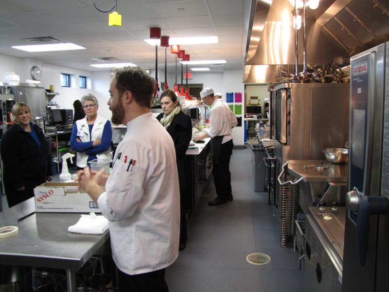 Justin Johnson gives hospital employees tour as chefs prepare patient meals in background