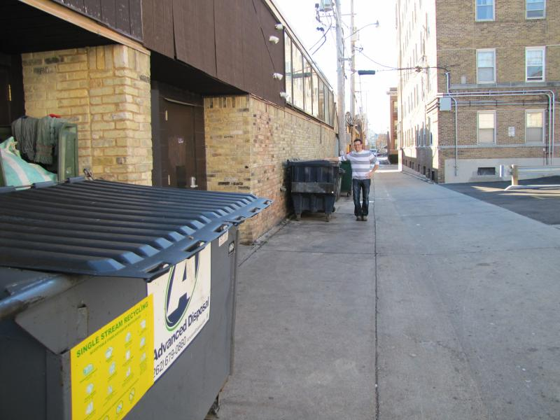 John Rossetto awaits a super-size compost dumpster behind his restaurant on Downer Avenue.