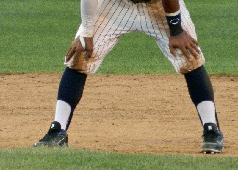 A baseball player wears stirrup socks, a decorative colored sock over a white long sock.