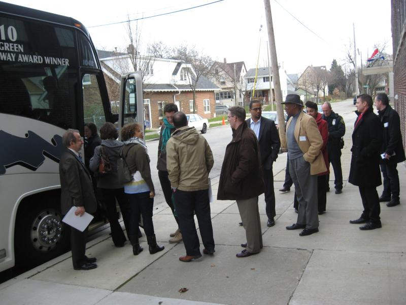 LISC Milwaukee Executive Director Leo Ries (far left) welcomes residents, policymakers, business owners and community partners aboard the bus tour of the Harambee neighborhood.