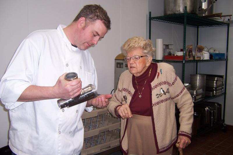 Nate Chappell, Executive Chef of The Trout House, discusses the technique for grinding potatoes with Betty Betenz, who has passed her recipe along to the restaurant.