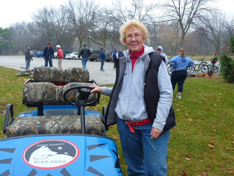 "Musher Judy Akerley shows off the ""Tundra Tracker,"" an all-terrain vehicle that lets the dogs give rides even without snow on the ground."