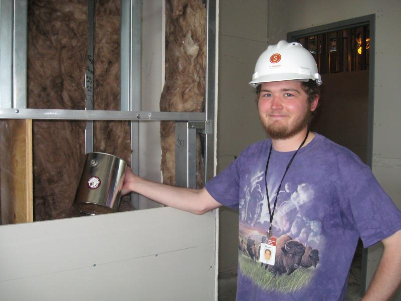 Circulation Assistant Harper Robison placing the time capsule in the wall of the East Library.