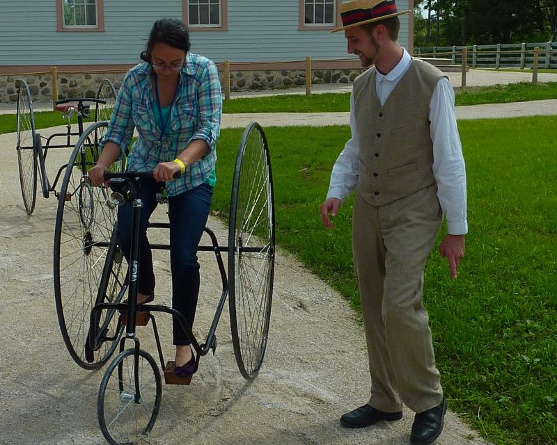 """Catch Wheel Fever"" interpreter lead Ryan Schwartz offers some tips to Lake Effect's Stephanie Lecci on how not to take a ""header"" on an old-fashioned tricycle."