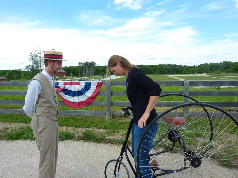 """Catch Wheel Fever"" interpreter lead Ryan Schwartz gives Lake Effect intern Audrey Nowakowski some instruction on how to get on her recreation tricycle."
