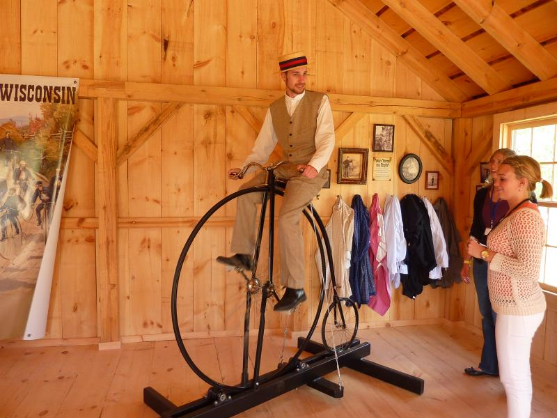 """Catch Wheel Fever"" interpreter lead Ryan Schwartz demonstrates how to get up on the high-wheel bicycle."