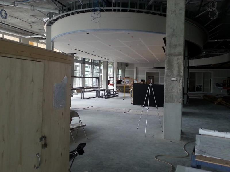The front entrance and conference room of the East Library. The conference room will have adjustable walls that will act as doors. When the conference room is not in use, the walls will be swiveled out to bring in natural light.