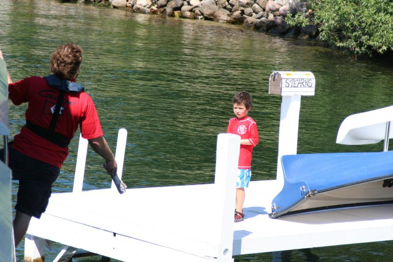 As a pier approaches, Garrett Robers hangs on the outside of the boat until it's time to jump to the dock. A young boy is one of the many lakefront residents who've come out to greet the mail boat.