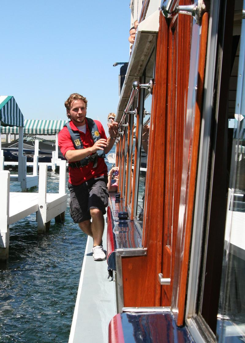 After mail jumpers leap onto the boat, they use a narrow ledge and handrail to walk to the front of the boat.