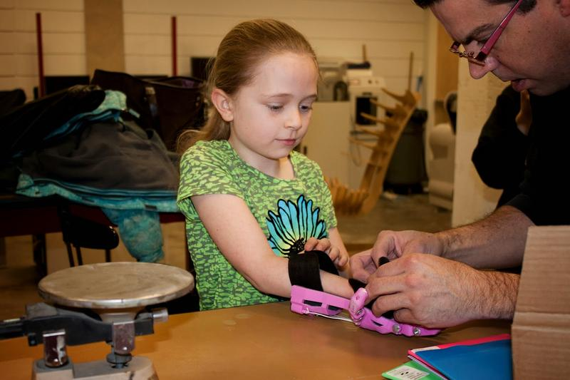 Frankie Flood helps Shea Stollenwerk get fitted for a new prosthetic hand