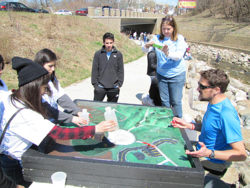 Scientist Peter Levi (far right) demonstrates how a watershed is impacted by pollution.