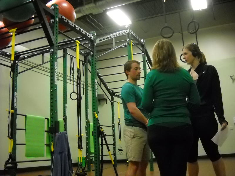 """Dr. Daniel Schumann, Lisa McNeil, and Audrey Nowakowski in front of """"The Beast"""" at the Momentum Movement Clinic in Brookfield, WI."""