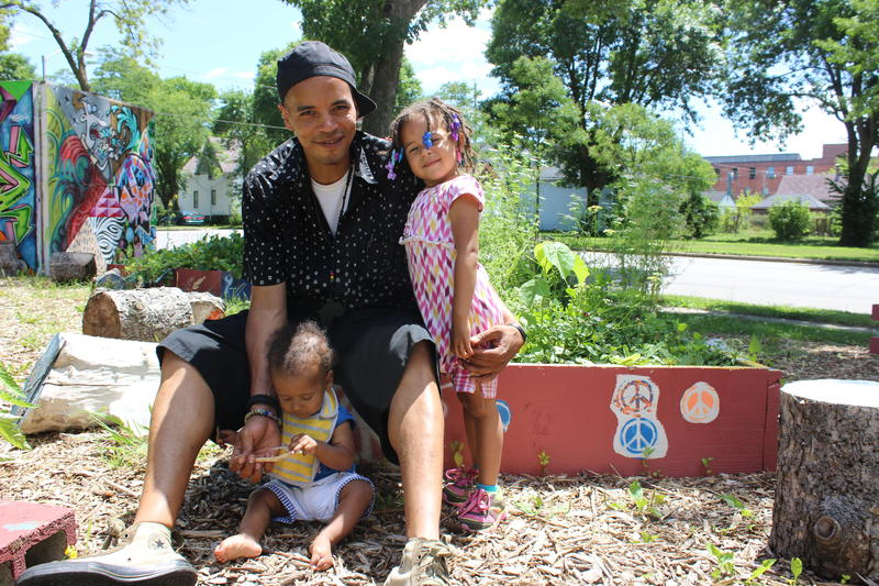 Fidel Verdin, co-founder of Summer of Peace, with his two children at the Peace Park and Garden, which he created.