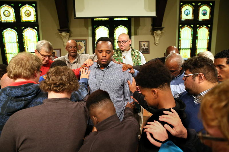Men from All Peoples Church surround 24 year old Isiah Johnson in prayer. It's a show of   solidarity and commitment to keeping Isiah safe after surviving two shootings in one year.