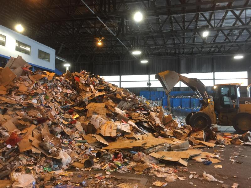 A front-end loader manages heaps of recyclables that trucks dump at the Materials Recovery Facility in Milwaukee.