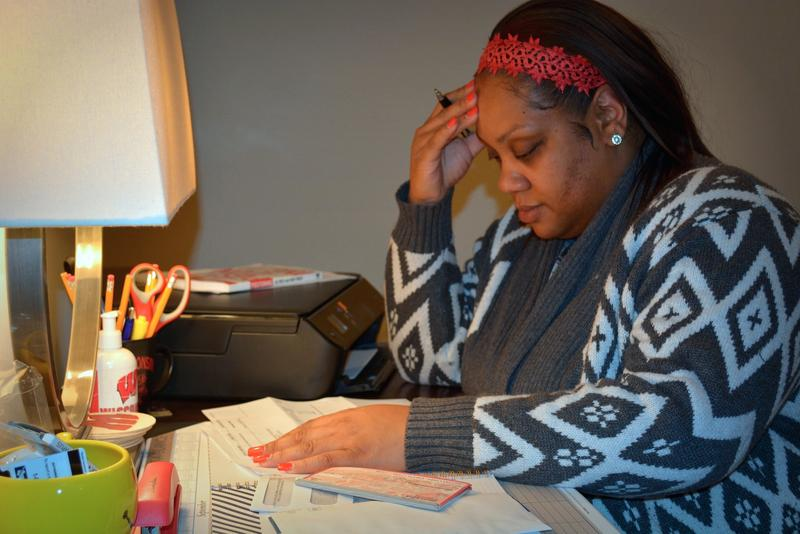 Latoya S. sits at her desk looking through overdue bills. Since 1998, she's taken out close to 20 short-term payday loans.