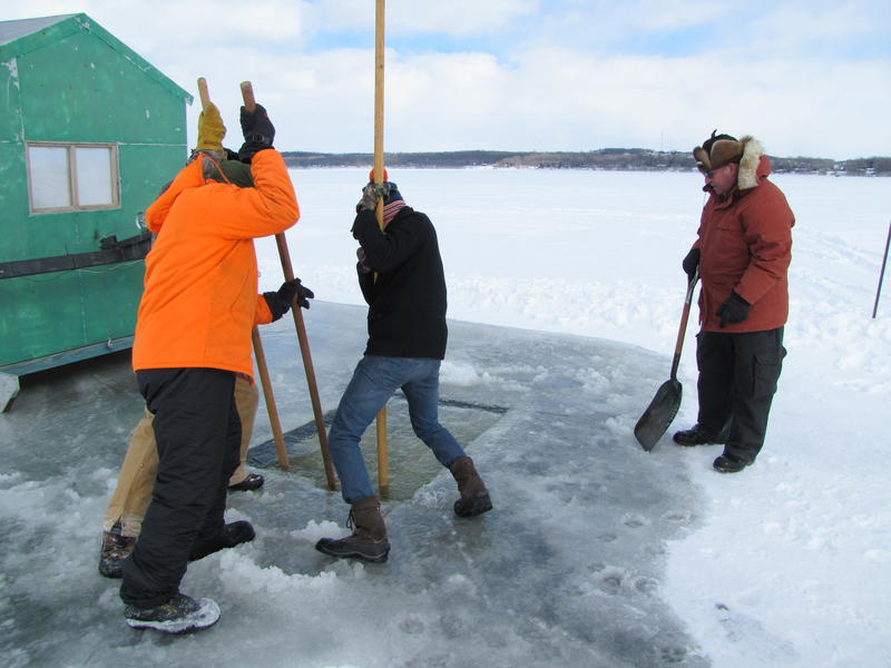 Pushing the ice block away and under the frozen lake.